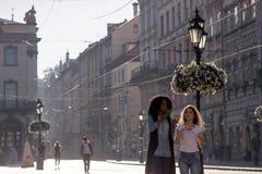 Dwa pięknej dziewczyny chodzi w śródmieściu z bąbel dmuchawami Jeden dziewczyna jest czarna z ładnym kędzierzawym włosy obrazy stock