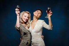 Dwa pięknej dziewczyny ono uśmiecha się w wieczór sukniach, trzyma win szkła Zdjęcia Stock