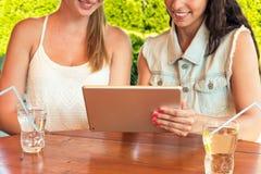 Dwa pięknej dziewczyny patrzeje pastylka komputeru osobistego komputer w cukiernianym outside obrazy stock