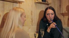 Dwa pięknej dziewczyny pije szampana i Dymi nargile w kawiarni zbiory