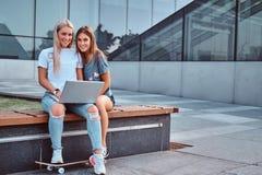 Dwa pięknej dziewczyny siedzi chwyty i patrzeje kamerę laptop podczas gdy siedzący na ławce na tle fotografia stock