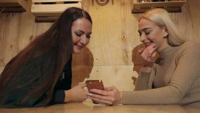 Dwa pięknej dziewczyny siedzi w kawiarni z telefonem i ono uśmiecha się zbiory wideo