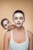 Dwa pięknej dziewczyny stosuje twarzową śmietanki maskę i Obrazy Royalty Free