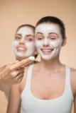 Dwa pięknej dziewczyny stosuje twarzową śmietanki maskę i Zdjęcie Royalty Free