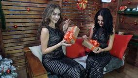 Dwa pięknej dziewczyny w czarnych sukniach z świątecznymi pudełkami w ich rękach Zdjęcie Stock