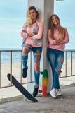 Dwa pięknej dziewczyny w modnym odziewają pozować z jeździć na deskorolce blisko poręczówki przeciw dennemu wybrzeżu obraz royalty free