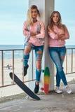 Dwa pięknej dziewczyny w modnym odziewają pozować z jeździć na deskorolce blisko poręczówki przeciw dennemu wybrzeżu fotografia royalty free
