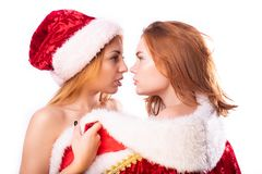 Dwa pięknej dziewczyny z czerwonym włosy w mitynkach i Święty Mikołaj kapeluszu fotografia stock