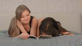 Dwa pięknej kobiety czyta magazyn przy badroom zdjęcie stock