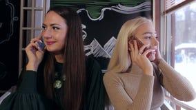 Dwa pięknej młodej dziewczyny opowiada na telefonie w kawiarni zbiory