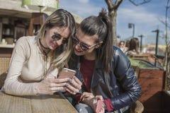 Dwa pięknej młodej kobiety ma zabawę outdoors podczas gdy używać ich smartphones obraz royalty free