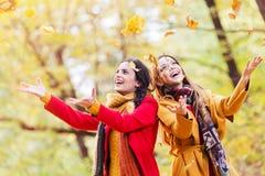 Dwa pięknej młodej kobiety rzuca liście w parku obraz stock