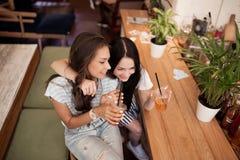 Dwa pięknej młodocianej uśmiechniętej dziewczyny z ciemnym włosy, ubierającym w przypadkowym stroju, ściskają each inny w wygodny zdjęcia stock