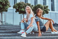 Dwa pięknej modniś dziewczyny siedzi na krokach z deskorolka na tle drapacz chmur zdjęcie royalty free
