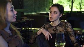 Dwa pięknej rozochoconej dziewczyny śmia się opowiadać przy barem nad napojami zbiory