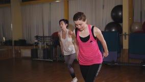 Dwa pięknej sport dziewczyny kucają w gym Dwa dziewczyny robi kroków aerobikom stać na czele lunge z dumbbells na platformie zdjęcie wideo