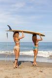 Dwa pięknej surfingowiec dziewczyny przy plażą iść w wodę Obrazy Royalty Free