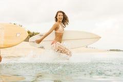 Dwa pięknej surfingowiec dziewczyny przy plażą iść w wodę Fotografia Royalty Free