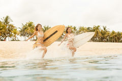 Dwa pięknej surfingowiec dziewczyny przy plażą iść w wodę Obraz Royalty Free