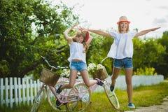 Dwa pięknej szczęśliwej modniś dziewczyny śmia się i pozuje dla kamery z rowerami Fotografia Royalty Free