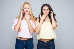 Dwa piękno przyjaciół kobiety opowiada na telefonach z szokować zdziwionymi emocjami na białym tle Zdjęcie Stock