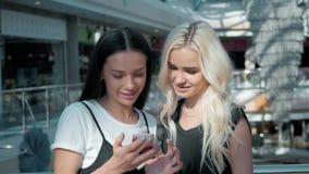 Dwa piękny młody żeński shopaholics surfuje internet w poszukiwaniu rabatów w zakupy centrum handlowym, młode studenckie dziewczy Obraz Stock