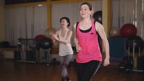 Dwa pi?knej sport dziewczyny kucaj? w gym Dwa dziewczyny robi krok?w aerobikom sta? na czele lunge z dumbbells na platformie zdjęcie wideo
