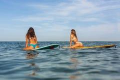 Dwa pięknej sporty dziewczyny surfuje w oceanie Zdjęcie Royalty Free