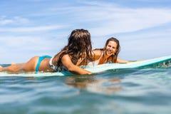 Dwa pięknej sporty dziewczyny surfuje w oceanie Zdjęcie Stock