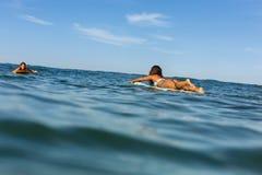 Dwa pięknej sporty dziewczyny surfuje w oceanie Obraz Royalty Free