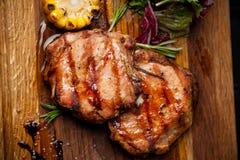 Dwa piec na grillu stki z kukurudzą i sałatką na drewnianej desce zdjęcie stock