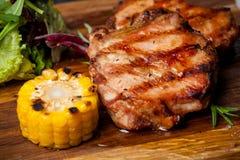 Dwa piec na grillu stki z kukurudzą i sałatką na drewnianej desce zdjęcie royalty free
