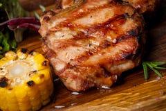 Dwa piec na grillu stki z kukurudzą i sałatką na drewnianej desce zdjęcia stock