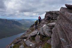 Dwa piechura travering grań wlec przegapiać jezioro w Szkockim H Zdjęcie Stock
