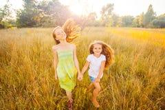Dwa pięknej siostry biega na gazonie w natura parku plenerowym w lecie Wolność i beztroski Obraz Royalty Free