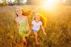 Dwa pięknej siostry biega na gazonie w natura parku plenerowym w lecie Wolność i beztroski Zdjęcia Royalty Free
