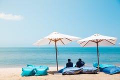 Dwa plażowego łóżka i białego parasol na tropikalnej plaży Zdjęcie Stock