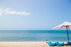 Dwa plażowego łóżka i białego parasol na tropikalnej plaży Obraz Stock