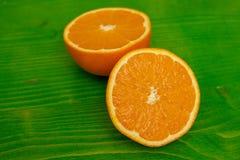 Dwa połówki dojrzała pomarańcze na zieleni ziemi fotografia stock