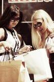 Dwa potomstwa fasonują kobiety z torba na zakupy przy centrum handlowym Zdjęcia Royalty Free