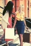 Dwa potomstwo mody kobiety z torba na zakupy na centrum handlowe krokach Zdjęcie Stock