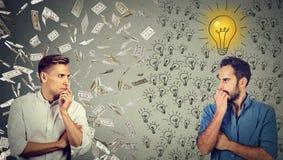Dwa poważnego biznesmena patrzeje each inny jeden pod pieniądze deszczem inny z jaskrawymi pomysłami zdjęcia royalty free
