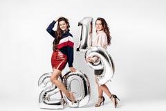 Dwa powabnej dziewczyny ubierającej w eleganccy mądrze ubrania trzymają balony w formie liczb 2019 na bielu fotografia stock