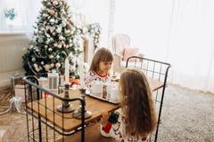 Dwa powabnej małej dziewczynki siedzą przy stołem i iść pić kakao z Marshmallows i ciastkami w wygodnym pokoju obraz stock