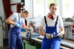 Dwa pracownik na pracy ławce w fabryce Fotografia Stock
