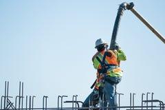 Dwa pracownika budowlanego nalewają cement w rebar zdjęcia stock