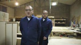Dwa pracownika chodzi i opowiada w meblarskiej fabryce z zbawczy gogle zdjęcie wideo