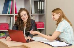 Dwa pracownika dyskutuje dokumenty biura szczęśliwie spojrzenie w laptop Obraz Royalty Free