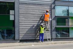 Dwa pracownika malują ścianę zdjęcia royalty free