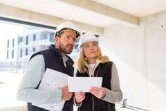 Dwa pracownika sprawdza po raz ostatni szczegóły na budowie Obrazy Stock